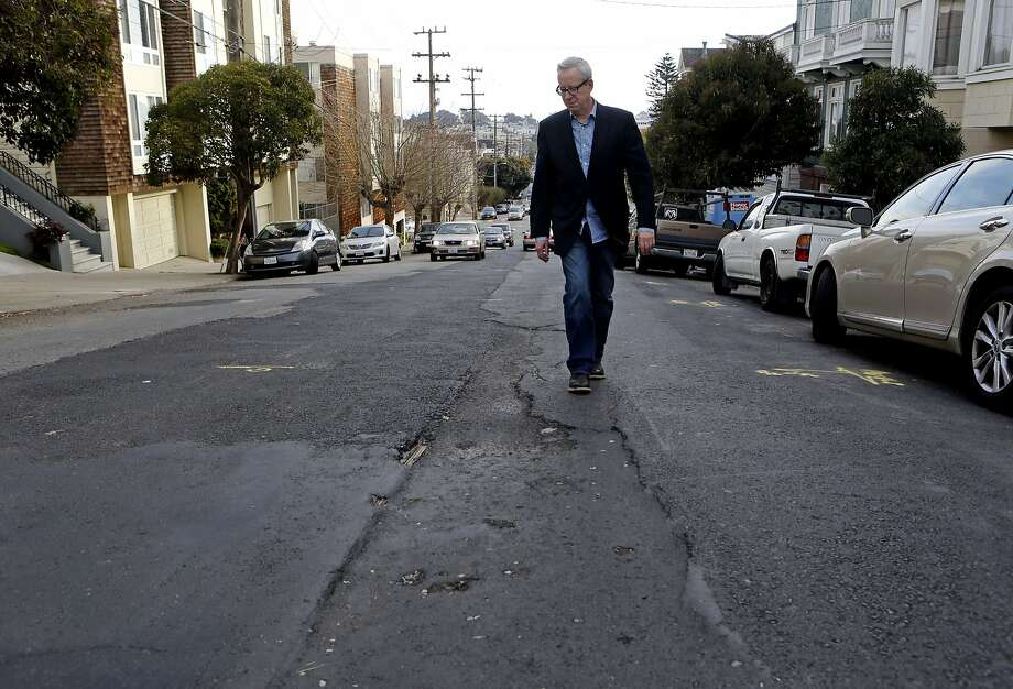 David Landis walks along the bumpy road that is now Scott Street after sewer repairs began in September. A temporary fix is slated to start by the end of the week. Photo: Michael Macor, The Chronicle