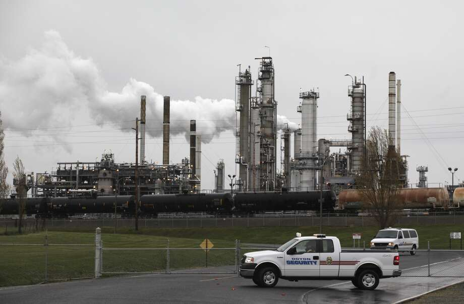Security vehicles are shown at the gate to a Tesoro Corp. refinery in Anacortes , Friday, April 2, 2010, after the rupture of a heat exchanger caused a fire that killed seven workers.  Tesoro has now reached a settlement with the U.S. Environmental Protection Agency that will upgrade pollution controls at the refinery, with major reductions in sulfur dioxide, nitrogen oxides, and carbon dioxide. (AP Photo/Ted S. Warren)