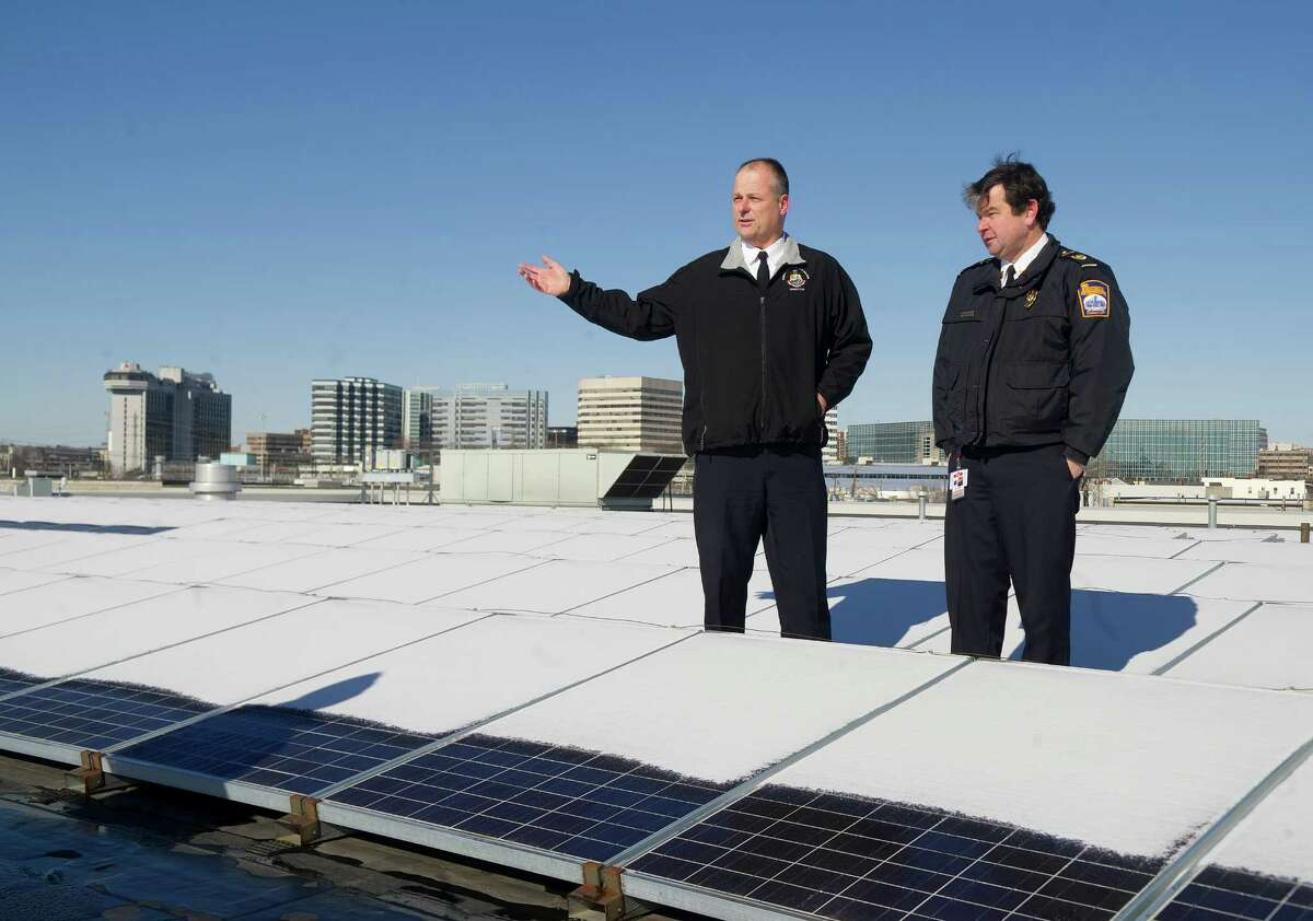 Stamford Director of Public Safety Ted Jankowski, left, and Fire Department Deputy Chief Trevor Roach, right, stand on the roof of the city's highway garage at 90 Magee Ave. in Stamford, Conn., surrounded by solar panels as they talk about the risks posed by the panels in firefighting situations on Wednesday, January 29, 2014.