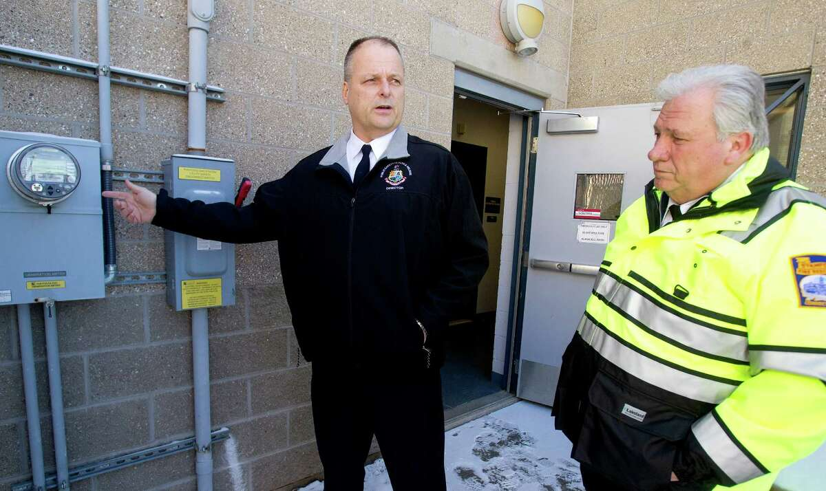 Stamford Director of Public Safety Ted Jankowski, left, and Fire Chief Peter Brown, right, look at the meter and emergency shut off switch for the solar panels on the roof of the city's highway garage at 90 Magee Ave. in Stamford, Conn., on Wednesday, January 29, 2014.