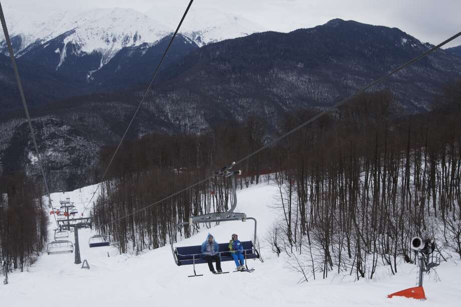 Volunteers move up on a ski lift at the Olympic area in Sochi, Russia. The Black Sea resort of Sochi will host the Winter Games Feb. 7-23. (AP Photo/Pavel Golovkin) Photo: Pavel Golovkin, Associated Press