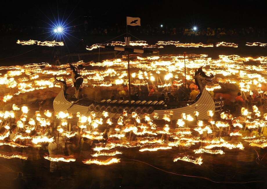 Thousand man march:Some 1,000 guizers, or men dressed as Vikings, carry torches as they march around their longboat during the annual Up 
