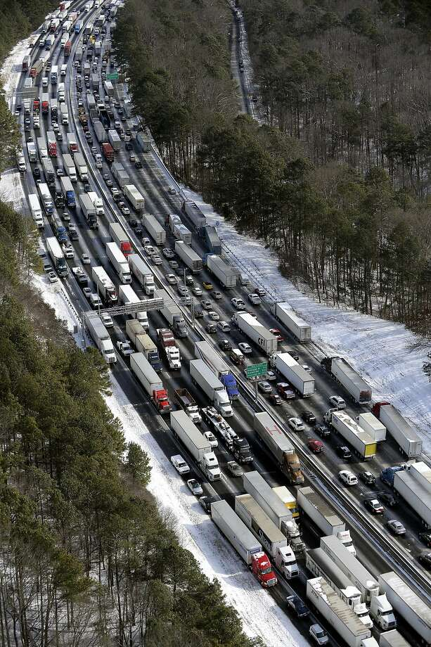 This aerial photo, traffic is snarled along the I-285 perimeter north of the metro area after a winter snow storm Wednesday, Jan. 29, 2014, in Atlanta.  Georgia Gov. Nathan Deal said early Wednesday that the National Guard was sending military Humvees onto Atlanta's snarled freeway system in an attempt to move stranded school buses and get food and water to people. Georgia State Patrol troopers headed to schools where children were hunkered down early Wednesday after spending the night there, and transportation crews continued to treat roads and bring gas to motorists, Deal said. (AP Photo/David Tulis) Photo: David Tulis, Associated Press
