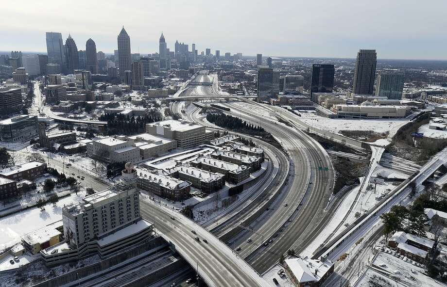 In this aerial view looking south toward downtown Atlanta, the ice-covered interstate system shows the remnants of a winter snow storm Wednesday, Jan. 29, 2014, in Atlanta. While such amounts of accumulation barely quality as a storm in the north, it was enough to paralyze the Deep South. (AP Photo/David Tulis) Photo: David Tulis, Associated Press