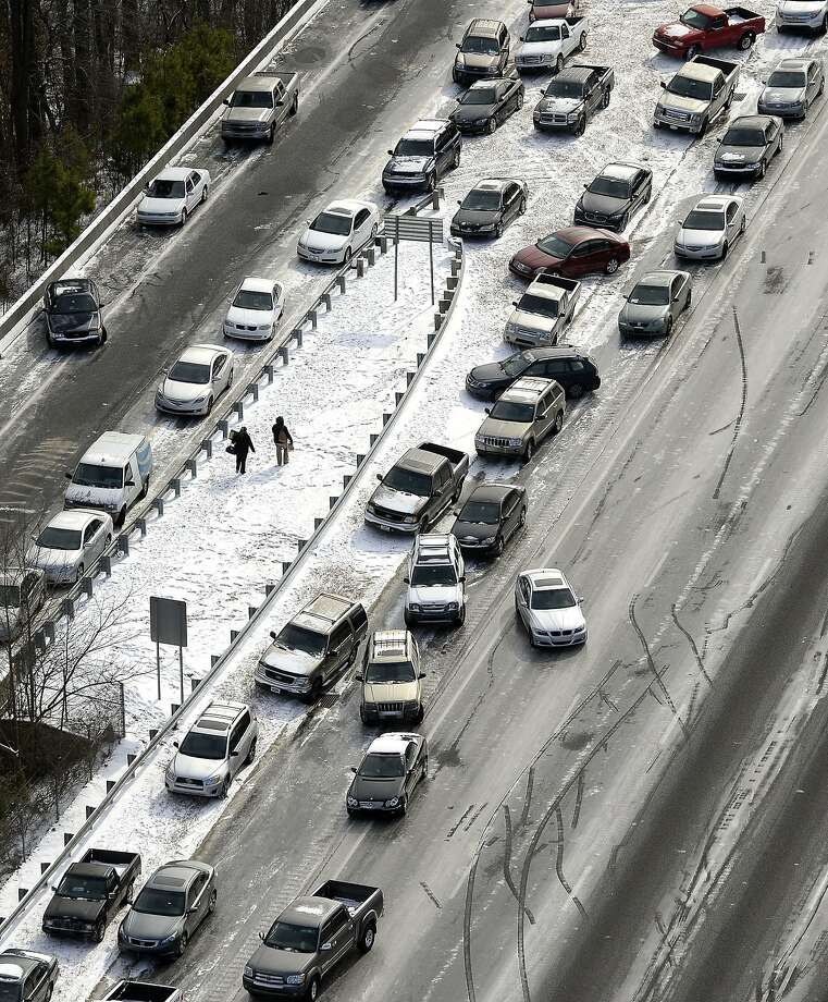 In this view looking at I-75 north at Mt. Paran Rd., abandoned cars are piled up on the median of the ice-covered interstate after a winter snow storm slammed the city with over 2 inches of snow that turned highways into parking lots creating massive traffic jams lasting through Wednesday, Jan. 29, 2014, in Atlanta. While such amounts of accumulation barely quality as a storm in the north, it was enough to paralyze the Deep South. (AP Photo/David Tulis) Photo: David Tulis, Associated Press