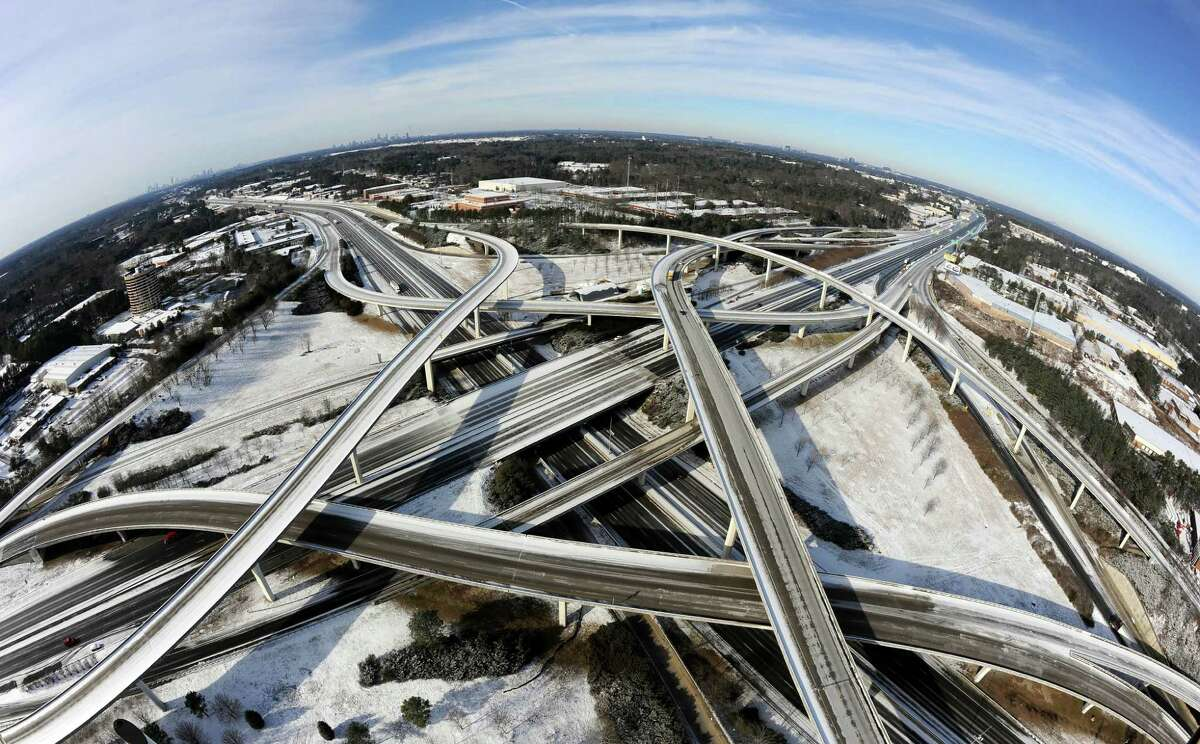 """In this photo taken with a fisheye lens over the city's perimeter highway known as """"Spaghetti Junction,"""" the ice-covered interstate system shows the remnants of a winter snow storm that slammed the city with over 2 inches of snow that turned highways into parking lots when motorists abandoned their vehicles creating massive traffic jams lasting through, Wednesday, Jan. 29, 2014, in Atlanta. While such amounts of accumulation barely quality as a storm in the north, it was enough to paralyze the Deep South. (AP Photo/David Tulis) ORG XMIT: GADT102"""
