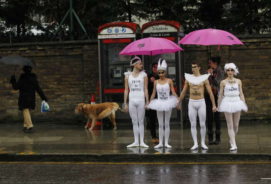 Dressed in tutus and tights, human rights activists wait to cross a London street to join a protest outside the Russian 