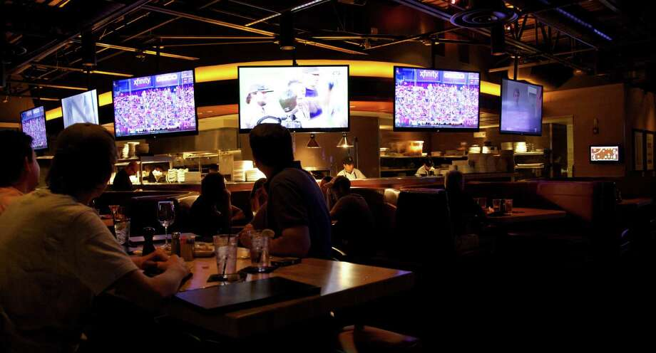 Guests at Cover 3 can watch the many TVs at the bar along Northwest Loop 1604. Photo: File Photos / San Antonio Express-News