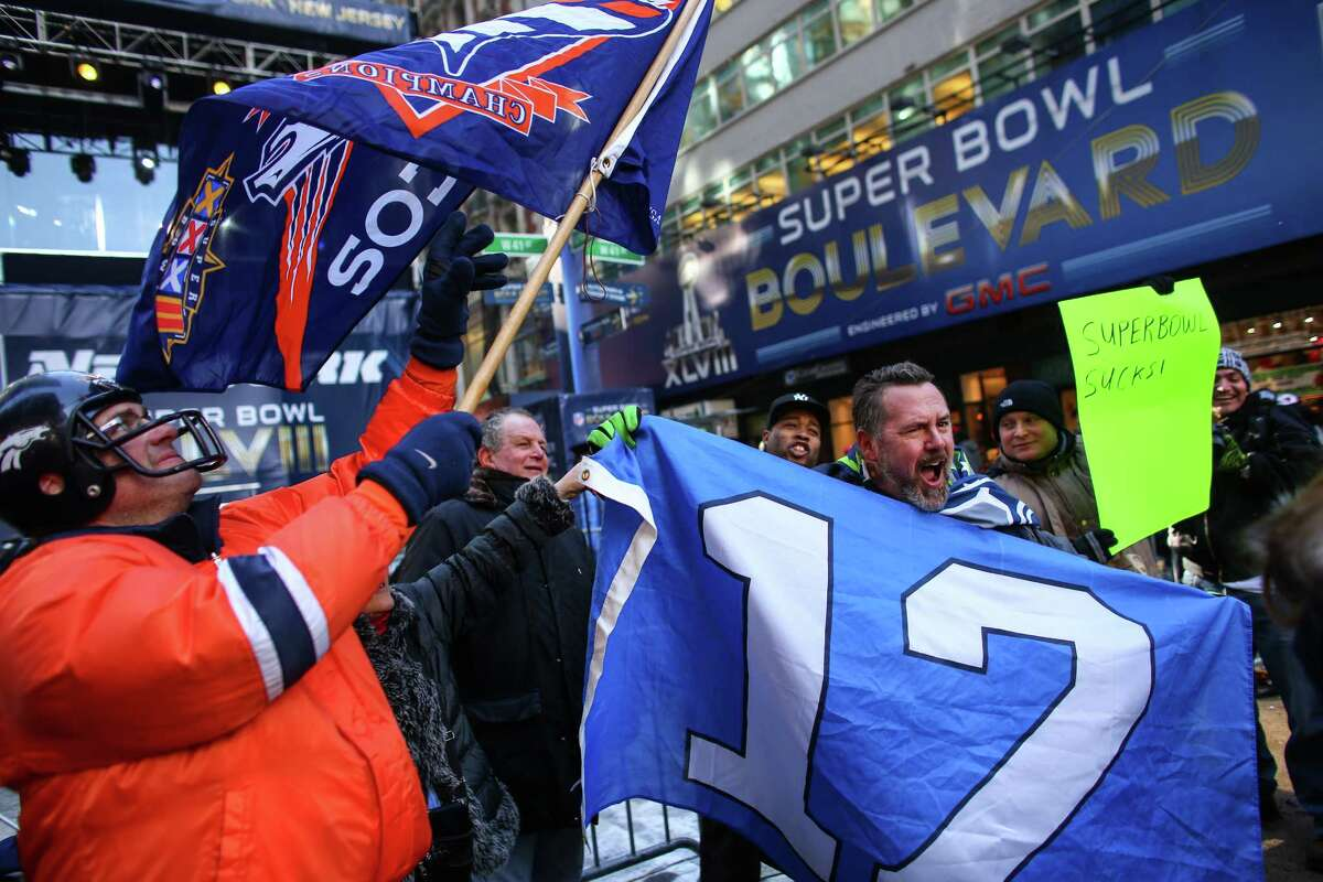 Denver Broncos fan Brian Carey hoists the Broncos flag as 12th Man Les Johnson of Rochester, Wash. waves the 12th Man flag during the Super Bowl Boulevard fan experience on Wednesday, January, 29, 2014. The NFL has turned 13 blocks of Broadway into a fan zone complete with games and attractions for NFL fans. Super Bowl hype continues to build in New York City in advance of Sunday's game between the Seattle Seahawks and Denver Broncos.