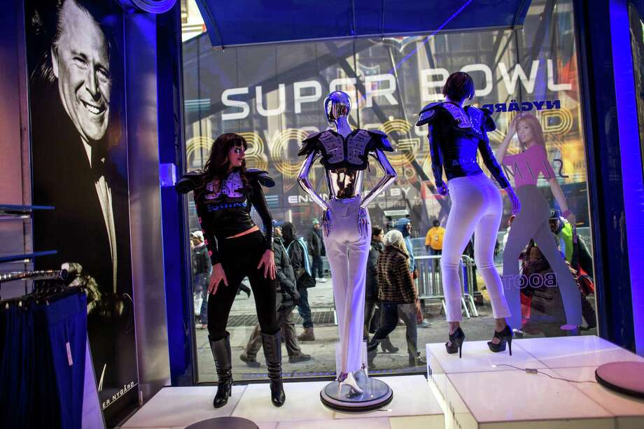 Dancers perform in the window of a women's clothing business as fans participate in the Super Bowl Boulevard experience.  The NFL has turned 13 blocks of Broadway into a fan zone complete with games and attractions for NFL fans. Super Bowl hype continues to build in New York City in advance of Sunday's game between the Seattle Seahawks and Denver Broncos. Photo: JOSHUA TRUJILLO, SEATTLEPI.COM / SEATTLEPI.COM