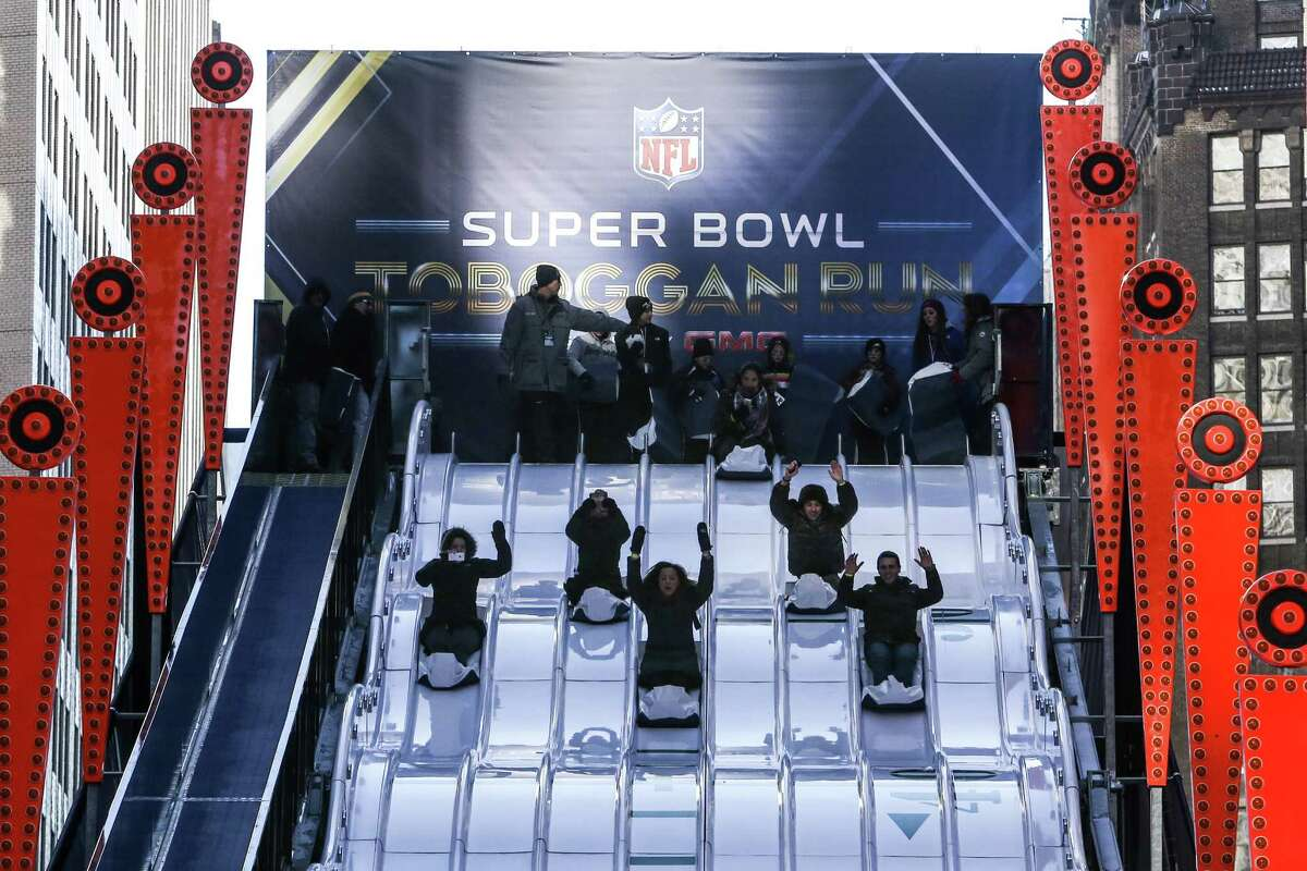 Participants ride the toboggan run during the Super Bowl Boulevard fan experience on Broadway.