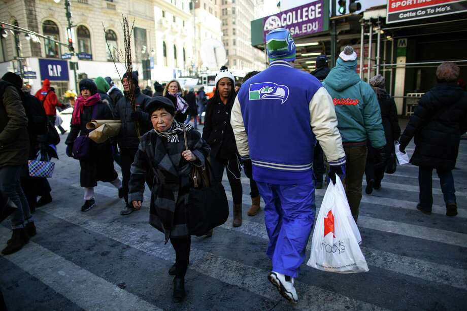 A Seahawks fan walks along Broadway during the Super Bowl Boulevard fan experience. Photo: JOSHUA TRUJILLO, SEATTLEPI.COM / SEATTLEPI.COM