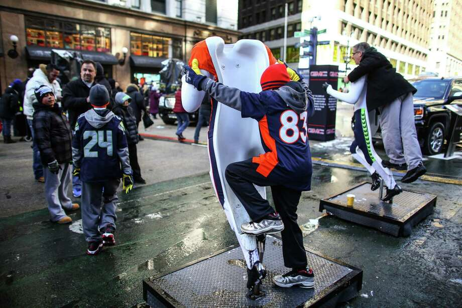 Fans pose for photos on mannequins during the Super Bowl Boulevard fan experience. Photo: JOSHUA TRUJILLO, SEATTLEPI.COM / SEATTLEPI.COM