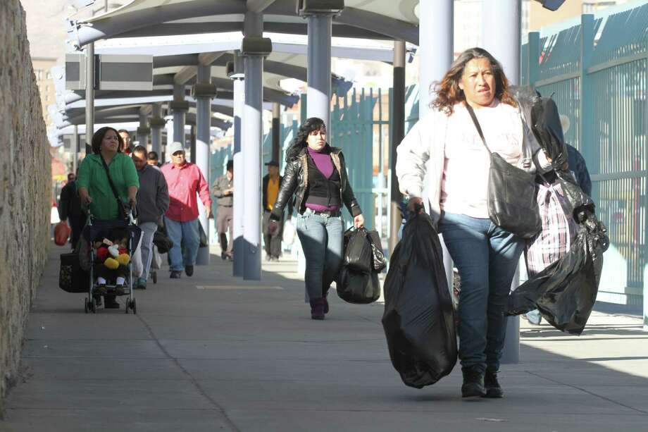 This Dec. 28, 2013 photo shows a shopper walking toward the Mexican border in El Paso, Texas. Sales tax will increase in Mexico in 2014 and that is expected to boost sales in U.S. border cities. (AP Photo/Juan Carlos Llorca) Photo: Juan Carlos Llorca, STF / AP