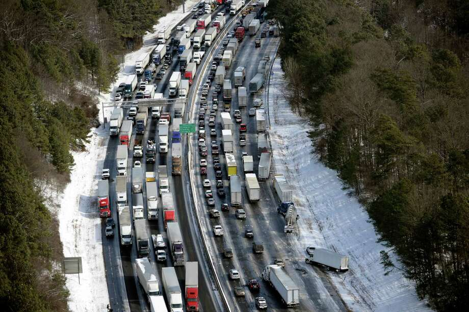 In this aerial photo, traffic is snarled along the I-285 perimeter north of the metro area after a winter snow storm, Wednesday, Jan. 29, 2014, in Atlanta.  Georgia Gov. Nathan Deal said early Wednesday that the National Guard was sending military Humvees onto Atlanta's snarled freeway system in an attempt to move stranded school buses and get food and water to people. Georgia State Patrol troopers headed to schools where children were hunkered down early Wednesday after spending the night there, and transportation crews continued to treat roads and bring gas to motorists, Deal said. (AP Photo/David Tulis) Photo: David Tulis, FRE / FR170493 AP