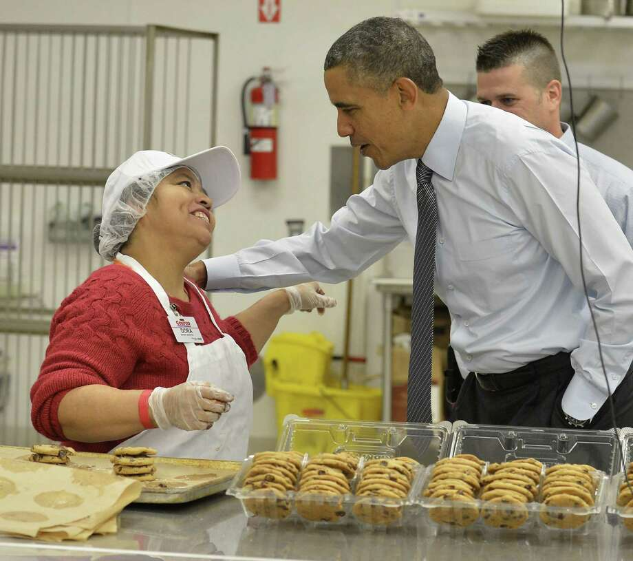 President Barack Obama greets a Costco bakery employee in Lanham, Md., as he takes his State of the Union address on a two-day tour outside Washington. Photo: Mike Theiler/Corbis, POOL / Abaca Press