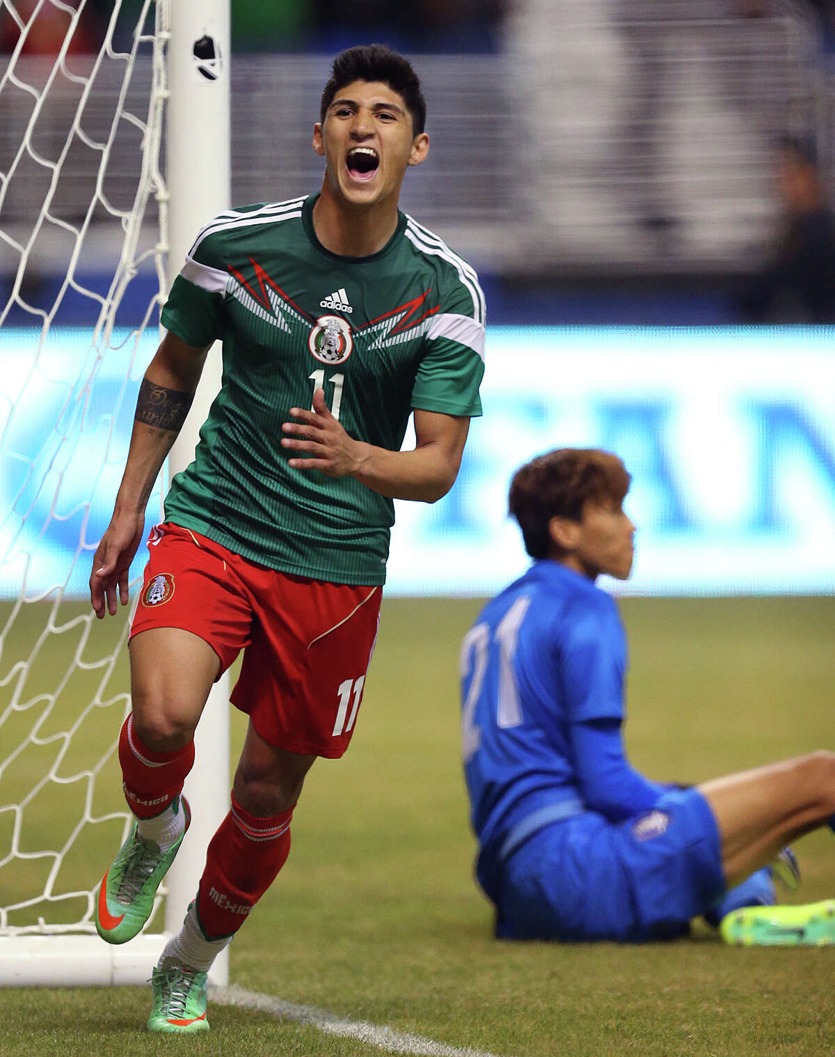 Mexico National Team forward Alan Pulido celebrates after scoring as South Korea goalkeeper Kim Seung-Gyu stays on the grass during the second half at the Alamodome, Wednesday, Jan. 29, 2014. Mexico beat Korea, 4-0.