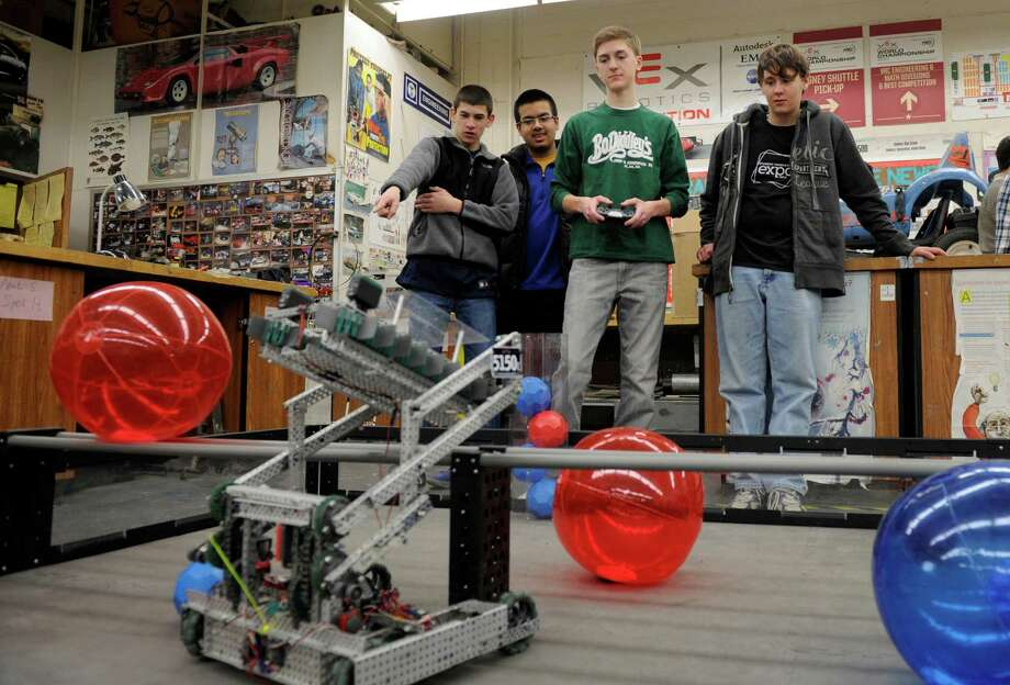 From left, Colin Lounsbury, 15,  Syed Hussain, 16, William Staib, 17, and Anthony Folino, 16, demonstrate their 5150E robot, Monday, January 27, 2014. This team from Danbury High School won the tournament championship in a recent state competition. Photo: Carol Kaliff / The News-Times