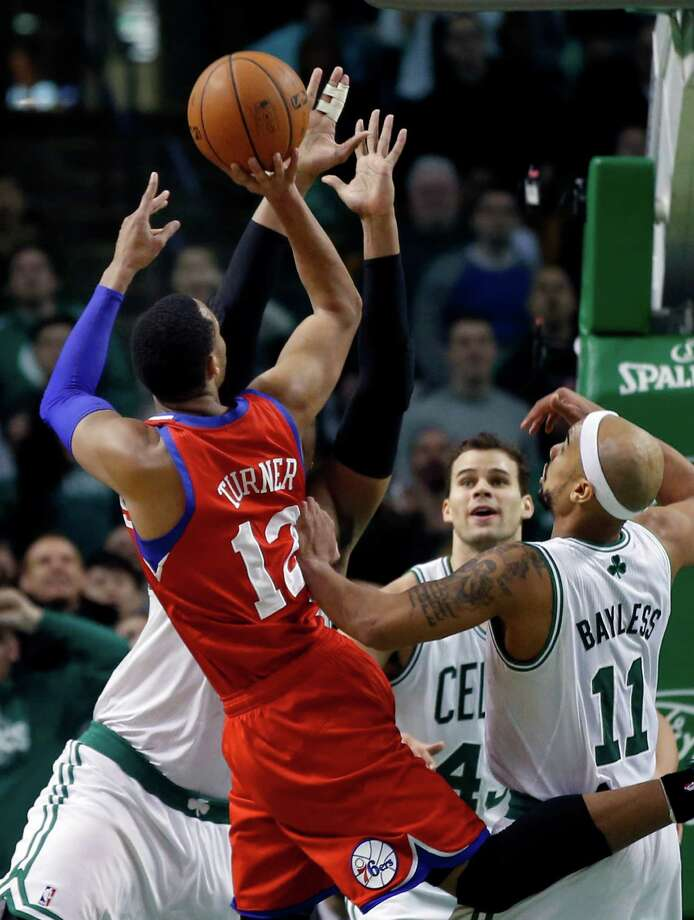 Philadelphia 76ers forward Evan Turner (12) shoots against the outstretched hands of Boston Celtics center Jared Sullinger, with Celtics center Kris Humphries (43) and point guard Jerryd Bayless (11) also defending, to win an NBA basketball game at the buzzer, 95-94, in Boston on Wednesday, Jan. 29, 2014. (AP Photo/Elise Amendola) ORG XMIT: MAEA108 Photo: Elise Amendola / AP