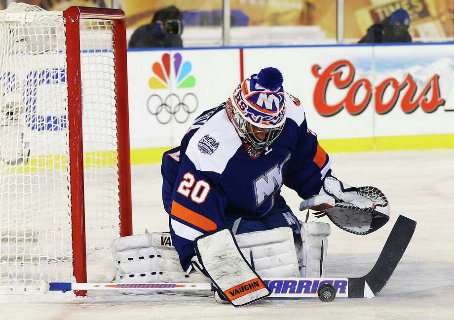 Islanders goalie Evgeni Nabokov sees the need to add to a stocking cap over his helmet as the temperature dipped to 18 degrees for Wednesday night's game against the Rangers at Yankee Stadium. Photo: Elsa, Staff / 2014 Getty Images