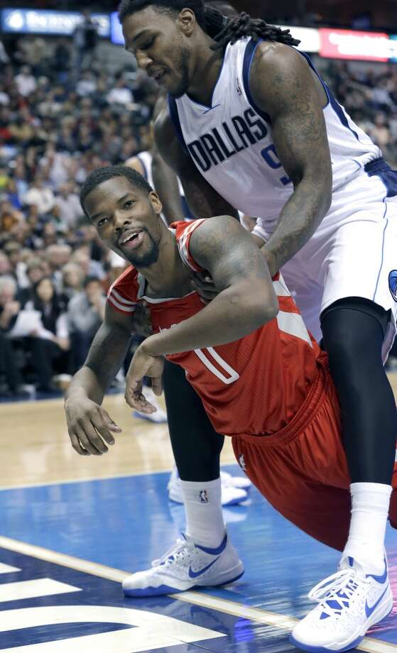 Rockets point guard Aaron Brooks (0) is picked up off the floor by Mavericks forward Jae Crowder (9) after Crowder fouled him. Photo: LM Otero, Associated Press