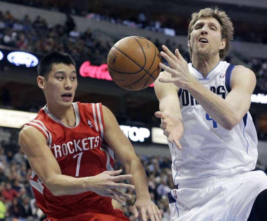 Rockets point guard Jeremy Lin (7) pass off the ball against Mavericks forward Dirk Nowitzki. Photo: LM Otero, Associated Press