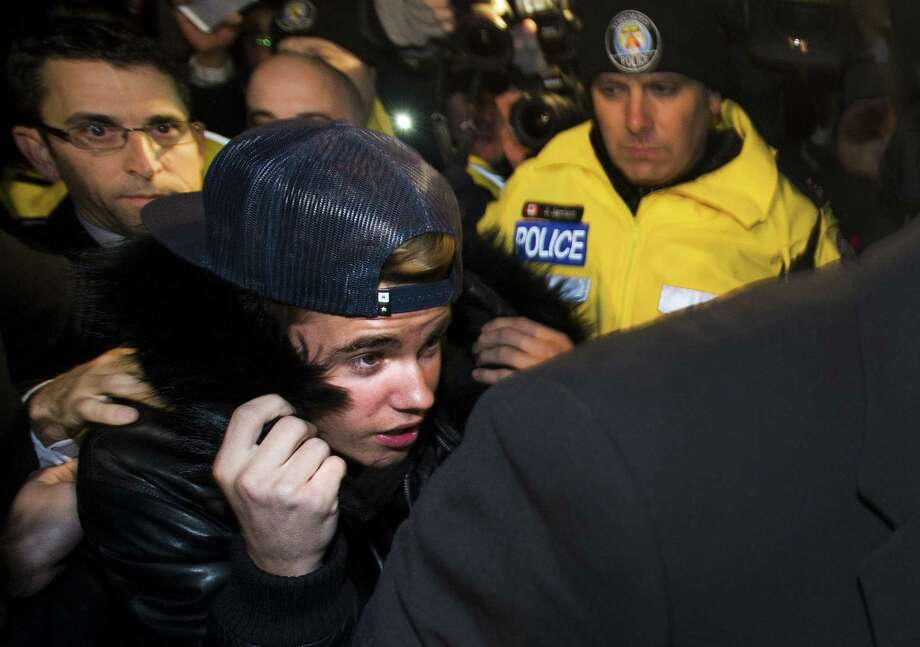 Canadian musician Justin Bieber is swarmed by media and police officers as he turns himself into city police for an expected assault charge in Toronto. Photo: Nathan Denette / Associated Press / CP
