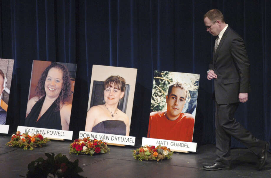 Jim Van Dreumel, husband of Donna Van Dreumel, walks past the photos of the Tesoro accident victims at a memorial in April 2010.  Donna, pictured at center, died in the blast that claimed six others. Photo: Scott Terrell / Skagit Valley Herald / AP2010