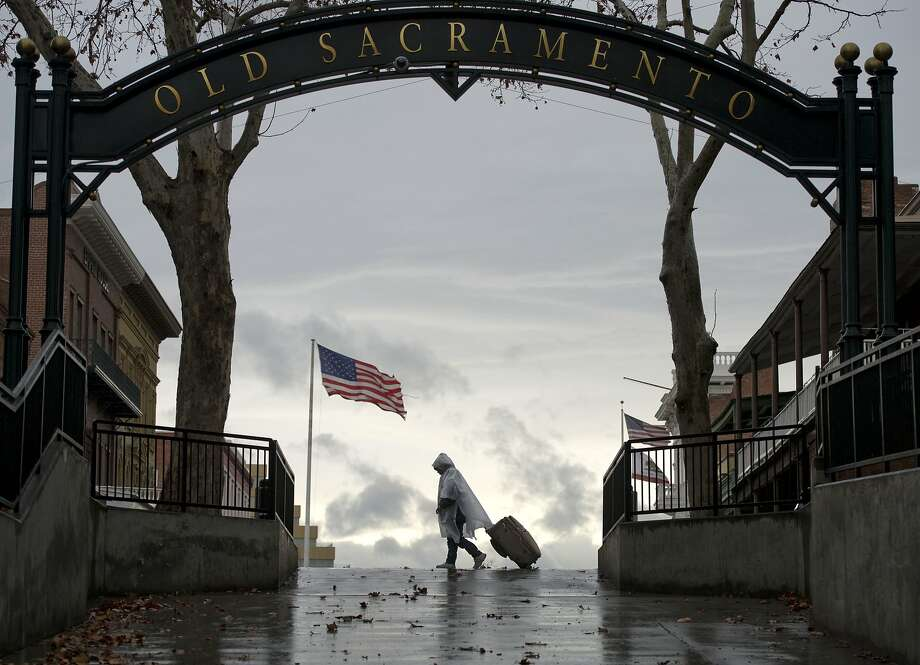 A pedestrian walks near the underpass that connects Old Sacramento with Downtown Sacramento during the first day of rain in 52 days on Wednesday, Jan. 29, 2014 in Sacramento, Calif. The National Oceanic and Atmospheric Administration's Web site is predicting a tenth of an inch of rain in San Francisco over the next two days and more than 2 inches in parts of Sacramento. (AP Photo/The Sacramento Bee, Hector Amezcua)  MAGS OUT; LOCAL TV OUT (KCRA3, KXTV10, KOVR13, KUVS19, KMAZ31, KTXL40); MANDATORY CREDIT Photo: Hector Amezcua, Associated Press