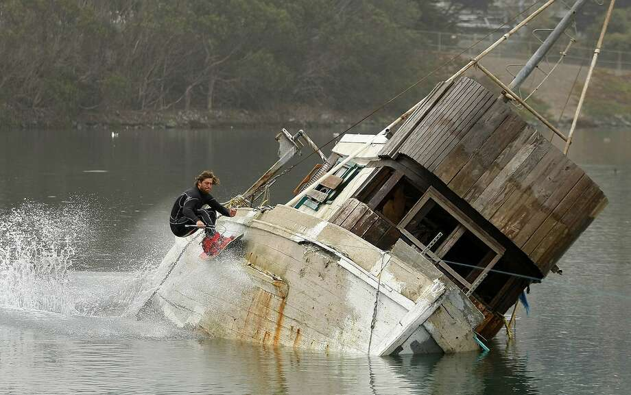 Hull banger: Trever Maur wakeboards off the side of derelict fishing boat during a King tide in the harbor of Moss Landing, 