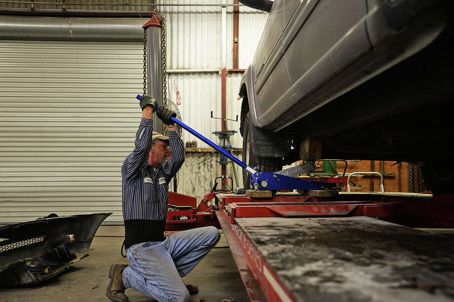Fasulo Paint and Body employee Chris Keith, left, works on a vehicle that was involved in an accident early Wednesday morning due to icy road conditions. Michael Rivera/@michaelrivera88