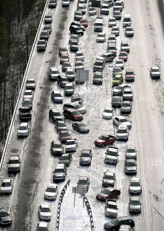 In this aerial photo, abandoned cars at I-75 headed northbound near the Chattahoochee River overpass are piled up in the median of the ice-covered interstate after a winter snow storm , Wednesday, Jan. 29, 2014, in Atlanta. Georgia Gov. Nathan Deal said early Wednesday that the National Guard was sending military Humvees onto Atlanta's snarled freeway system in an attempt to move stranded school buses and get food and water to people. Georgia State Patrol troopers headed to schools where children were hunkered down early Wednesday after spending the night there, and transportation crews continued to treat roads and bring gas to motorists, Deal said.  (AP Photo/David Tulis) Photo: David Tulis, Associated Press