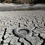 A discarded tire is seen stuck in the exposed lake bed of the Almaden Reservoir which is experiencing extremely low water levels due to the ongoing drought, in San Jose.
