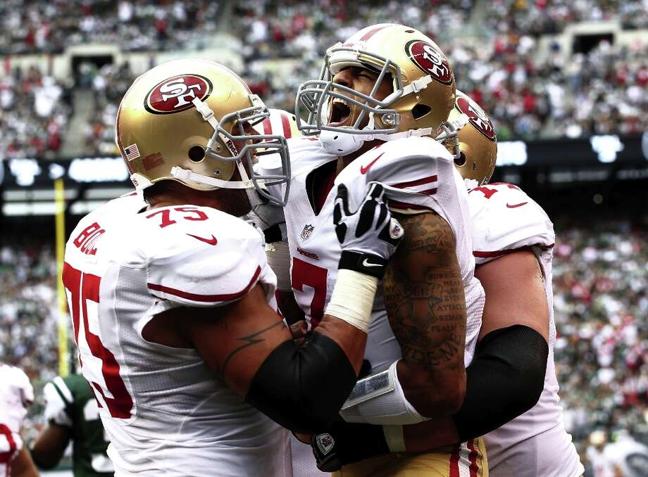 Colin Kaepernick celebrates a touchdown with Alex Boone and Joe Staley during a game against the New York Jets at MetLife Stadium on September 30, 2012 in East Rutherford, New Jersey. Photo: Jeff Zelevansky, Getty Images / 2012 Getty Images