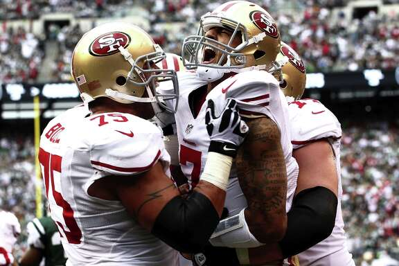Colin Kaepernick celebrates a touchdown with Alex Boone and Joe Staley during a game against the New York Jets at MetLife Stadium on September 30, 2012 in East Rutherford, New Jersey.
