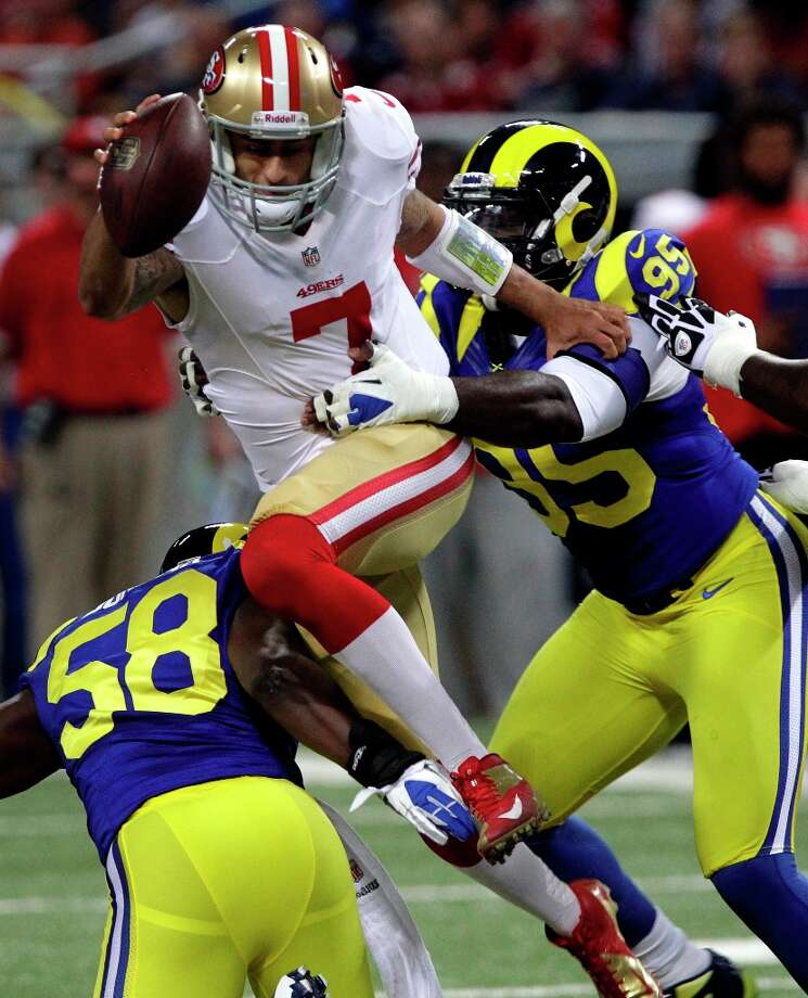 Kaepernick tries to leap away from St. Louis Rams outside linebacker Jo-Lonn Dunbar and defensive end William Hayes, right, during the first quarter of an NFL football game Sunday, Dec. 2, 2012, in St. Louis. Photo: Seth Perlman, Associated Press