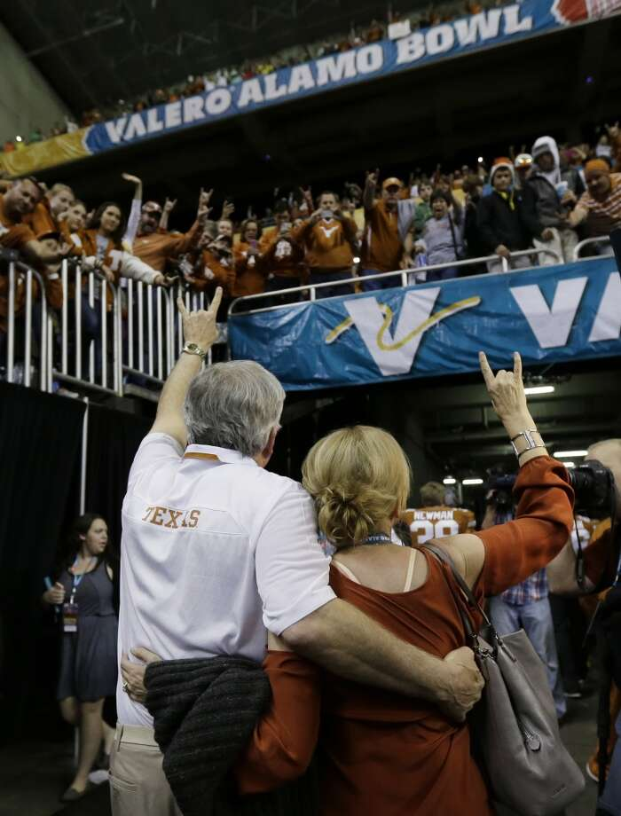Mack Brown, left, and his wife Sally, right, give the Hook'em Horns sign to fans as they leave the field after the Alamo Bowl. Photo: Eric Gay, Associated Press