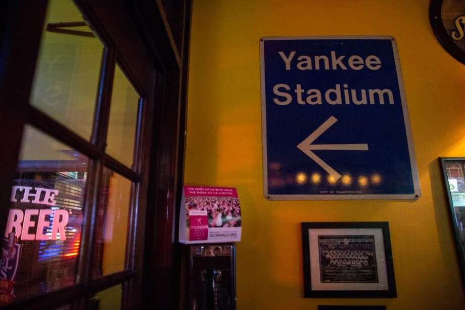 A sign for Yankee Stadium points out the door at Carlow East in the upper east side of Manhattan. The bar is known as a hub for people from Seattle. Photographed on Wednesday, January, 29, 2014. (Joshua Trujillo, seattlepi.com) Photo: SEATTLEPI.COM