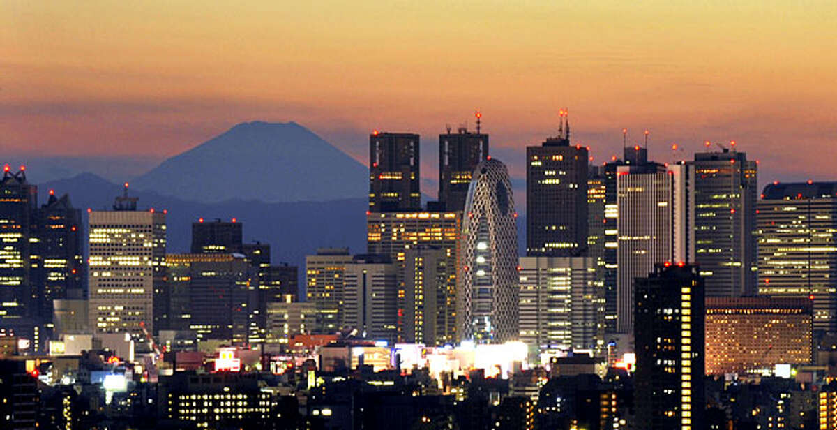 Japan's highest mountain Mount Fuji rises up behind the skyscraper skyline of the Shinjuku area of Tokyo at sunset on January 10, 2010.