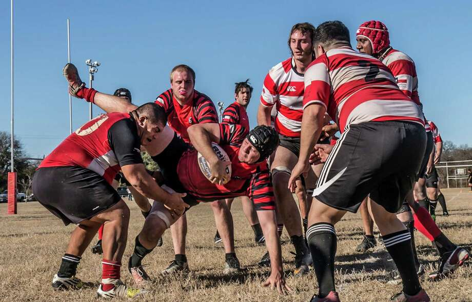 Sam Poindexter crashes to the ground after winning a lineout - an inbounds play in rugby - during a scrimmage of the San Antonio Rugby Club. Photo by Joshua Trudell//For the Express-News