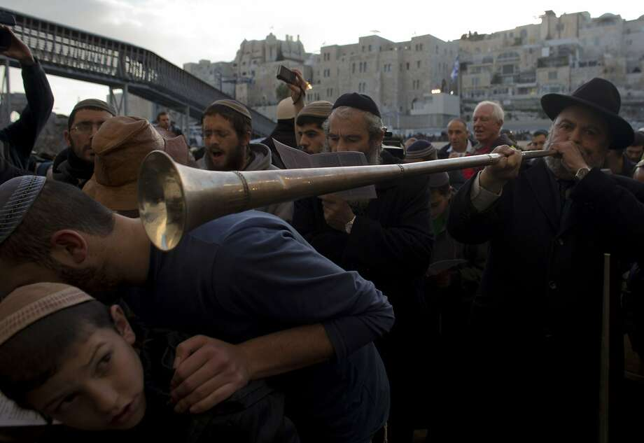 There go the walls of Jericho:Boys duck as an Israeli nationalist blasts a horn during a mass at the Western Wall 
