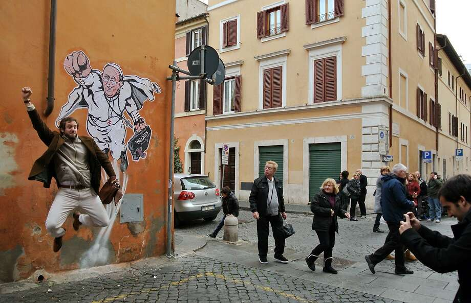 Caped crusader:A tourist poses for a picture in front of graffiti depicting Pope Francis as a flying superhero on a wall of the Borgo Pio district near St. Peter's Square in Rome. Photo: Gregorio Borgia, Associated Press