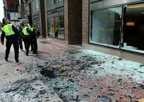 BOSTON - APRIL 15: Boston Police look at blown out windows at the scene of the first explosion on Boylston Street near the finish line of the Boston Marathon. Photo: Boston Globe, Getty Images / 2013 - The Boston Globe