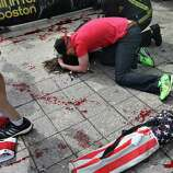 BOSTON - APRIL 15: (EDITOR'S NOTE: THIS IMAGE CONTAINS GRAPHIC CONTENT) A man comforts a victim on the sidewalk at the scene of the first explosion near the finish line of the 117th Boston Marathon. (Photo by John Tlumacki/The Boston Globe via Getty Images)