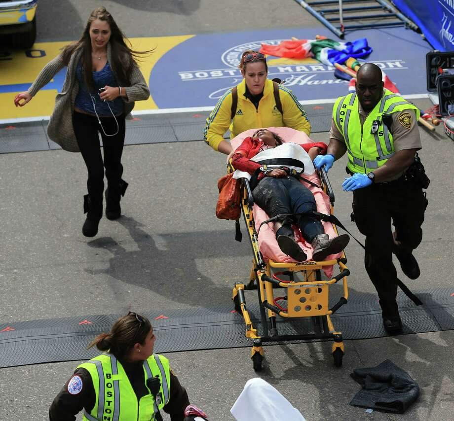 BOSTON - APRIL 15: A person who was injured in an explosion near the finish line of the 117th Boston Marathon is taken away from the scene on a stretcher. (Photo by David L. Ryan/The Boston Globe via Getty Images) Photo: Boston Globe, Wire / 2013 - The Boston Globe