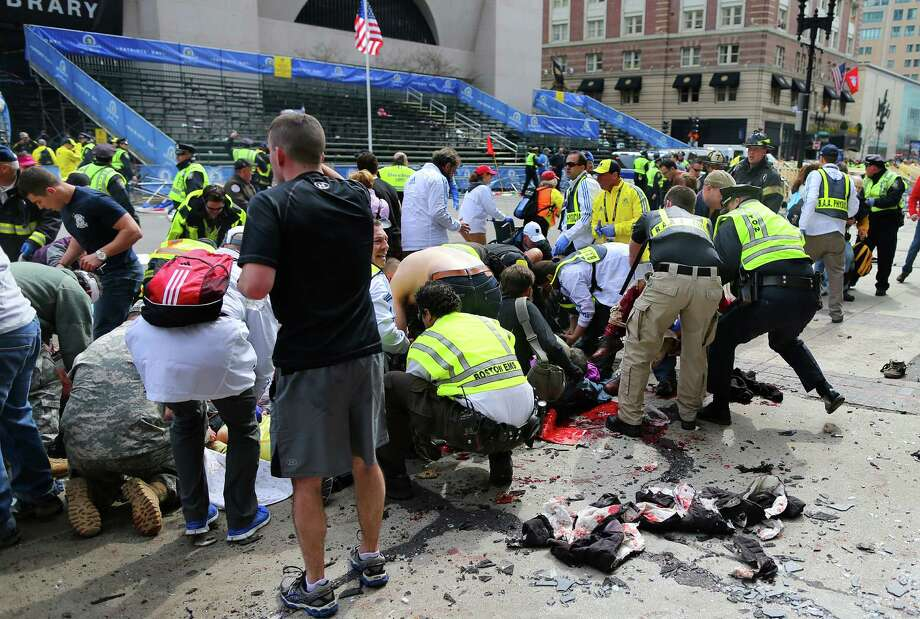 BOSTON - APRIL 15: The injured are helped at the scene of the first explosion on Boylston Street near the finish line of the Boston Marathon. Photo: Boston Globe, Getty Images / 2013 - The Boston Globe