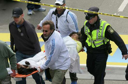 BOSTON - APRIL 15: (EDITOR'S NOTE: THIS IMAGE CONTAINS GRAPHIC CONTENT) A person who was injured in an explosion near the finish line of the 117th Boston Marathon is taken away from the scene on a stretcher. Photo: Boston Globe, Getty Images / 2013 - The Boston Globe