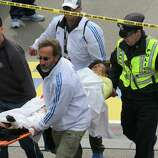 BOSTON - APRIL 15: (EDITOR'S NOTE: THIS IMAGE CONTAINS GRAPHIC CONTENT) A person who was injured in an explosion near the finish line of the 117th Boston Marathon is taken away from the scene on a stretcher.