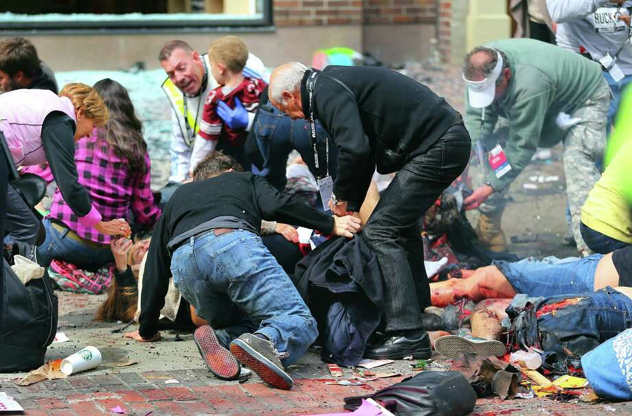 BOSTON - APRIL 15: (EDITOR'S NOTE: THIS IMAGE CONTAINS GRAPHIC CONTENT) A young boy (rear) is comforted as injured people are tended to on the sidewalk of Boylston Street after two explosions went off near the finish line of the 117th Boston Marathon on April 15, 2013. Photo: Boston Globe, Getty Images / 2013 - The Boston Globe