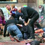 BOSTON - APRIL 15: (EDITOR'S NOTE: THIS IMAGE CONTAINS GRAPHIC CONTENT) A young boy (rear) is comforted as injured people are tended to on the sidewalk of Boylston Street after two explosions went off near the finish line of the 117th Boston Marathon on April 15, 2013.